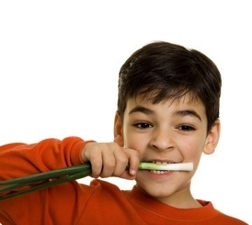 Boy eating spring onions - scallions