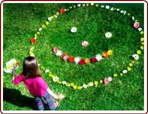 Teaching nature to kids - young girl making a flower face