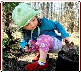 Teaching kids to garden - Small girl digging with trowel