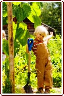 Helping children love nature - Small boy helping in garden