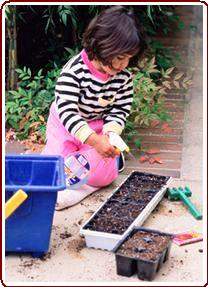Helping children garden - Girl learning how to plant vegetables