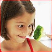 Girl eating broccoli on fork